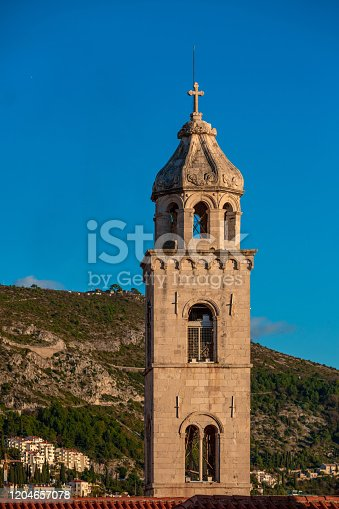 Medieval catholic church tower with bell cote, hills on background