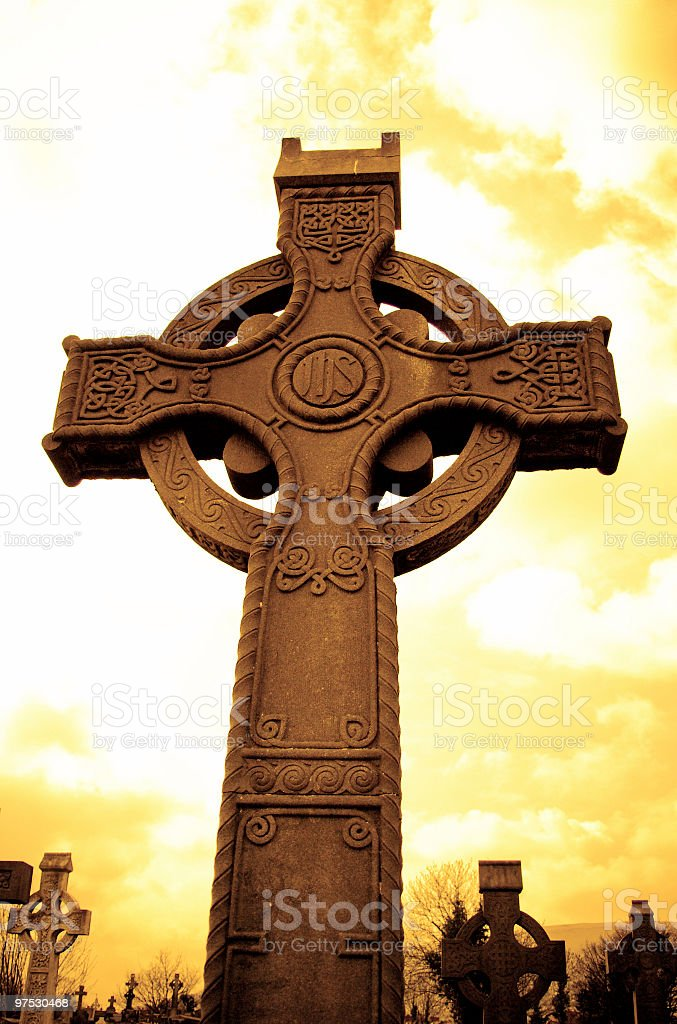Medieval Celtic Cross with sunset colors in Irish cemetery royalty-free stock photo