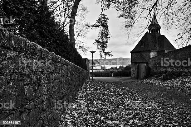 Photo of Medieval chapel by a leaf-covered gravel road