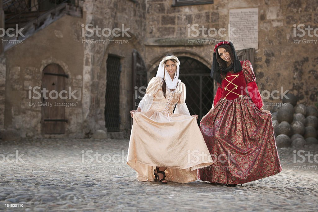 Medieval Damsels dancing in a historical Court Yard stock photo