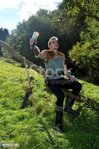630040004istockphoto Medieval dressed man, holds drinking horn high in the hand 635975160