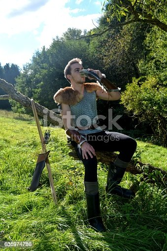 630040004istockphoto Medieval dressed man, sits on branch, drinks from drinking horn 635974786