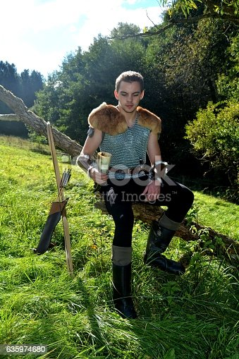 630040004istockphoto Medieval dressed one man, holds drinking horn high in  hand 635974680