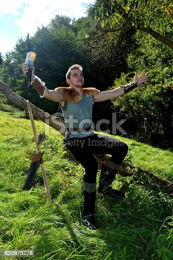 630040004istockphoto Medieval dressed one  man, with  drinking horn ,  arms stretched out 635975278