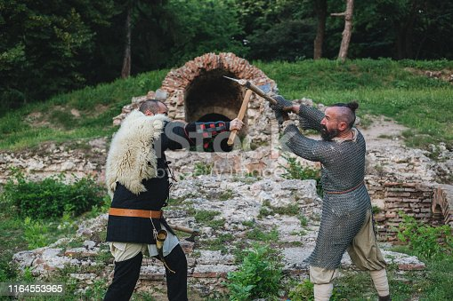 istock Medieval fighting with axes 1164553965