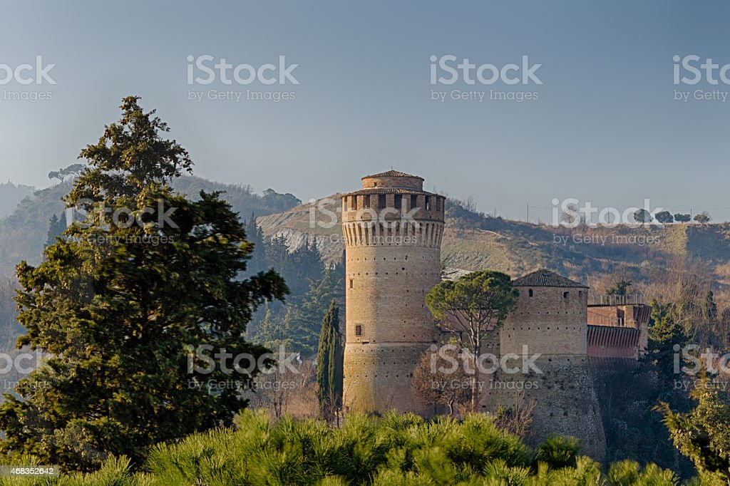 Medieval  Fortress and clock tower among hills in the fog royalty-free stock photo