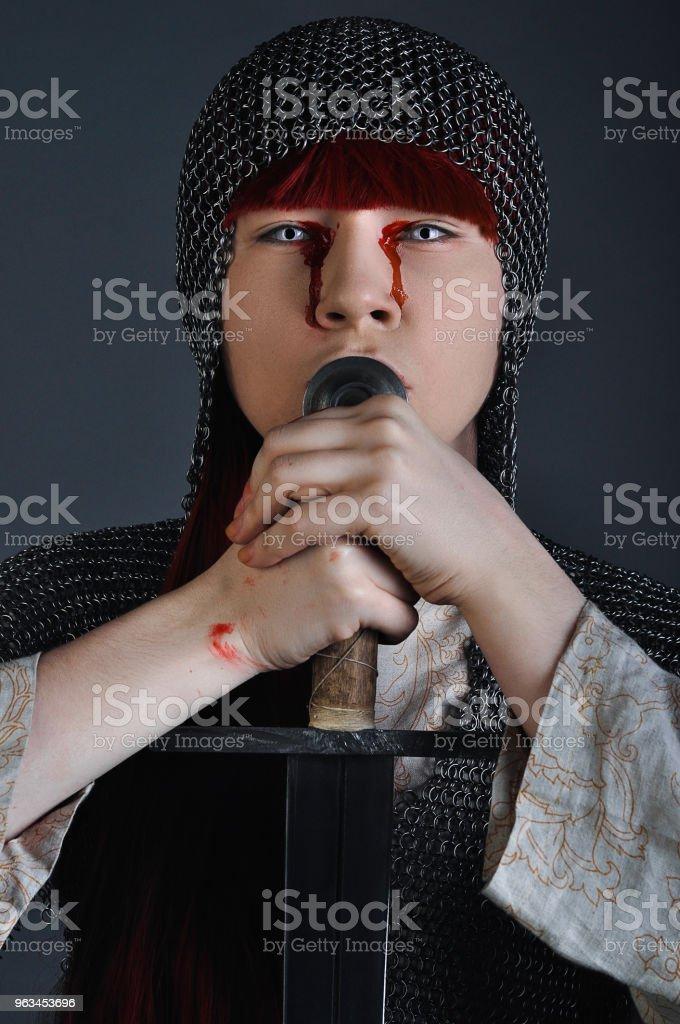 Zincirden Kızıl saçlı kılıçlı Ortaçağ kız gri bir arka plan üzerinde kanla ellerinin üzerinde duruyor - Royalty-free Antik Stok görsel