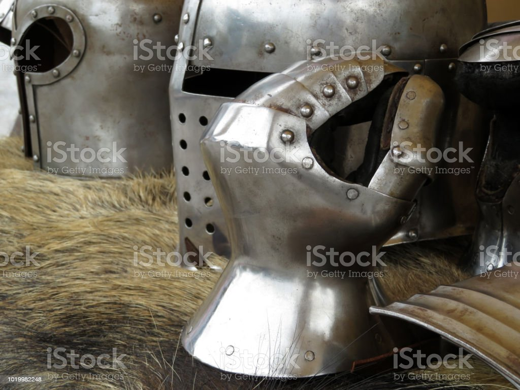 Medieval helmets and gloves on a bearskin rug. Armor of middle ages, knightly equipment, armory forge stock photo