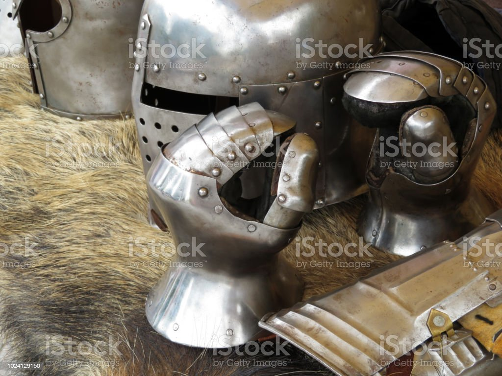 Medieval helmets and gloves on a bearskin rug stock photo