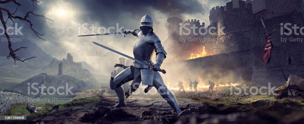 Medieval Knight In Armour Holding Two Swords Near Burning Castle stock photo