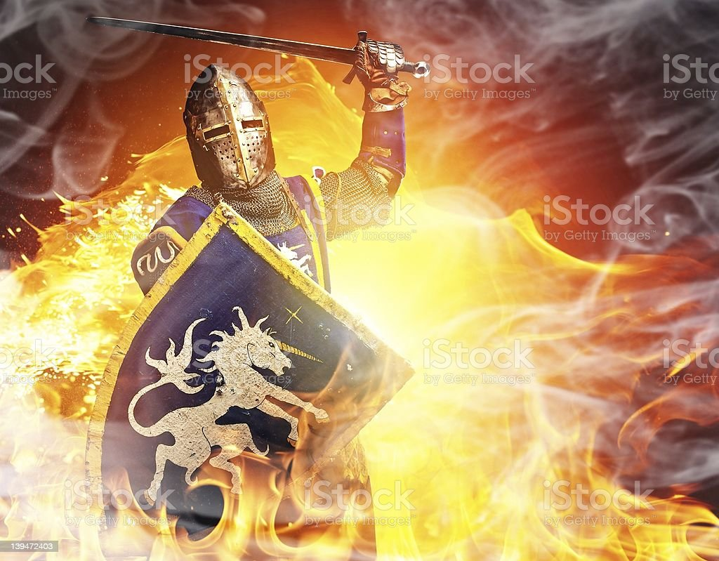Medieval knight in attack position on fire background. stock photo