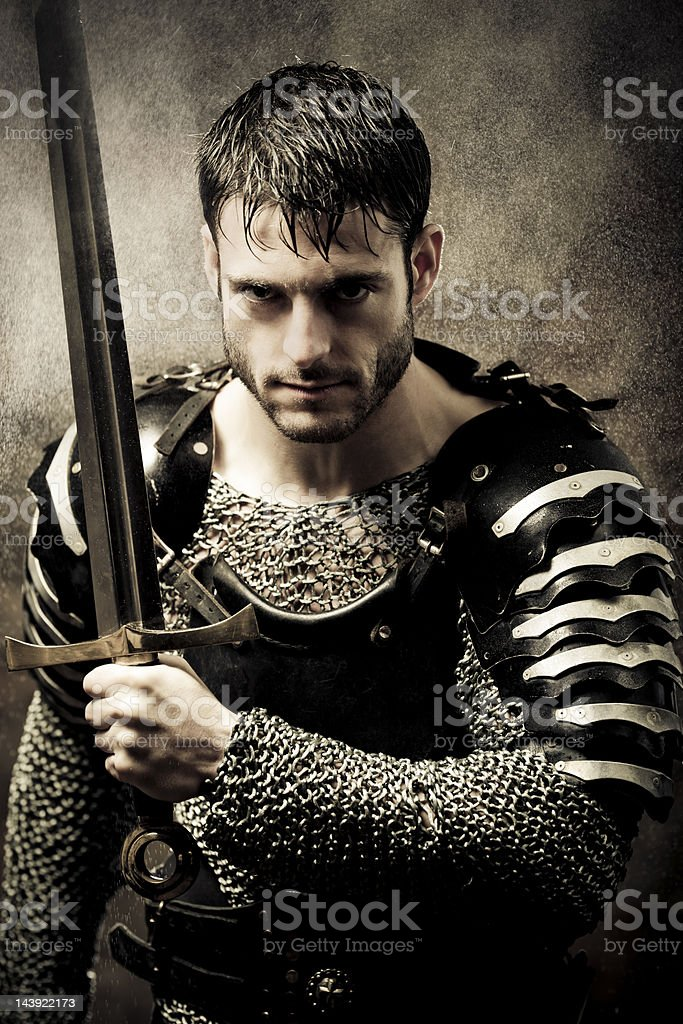 Medieval Knight in the rain launching an offensive stock photo