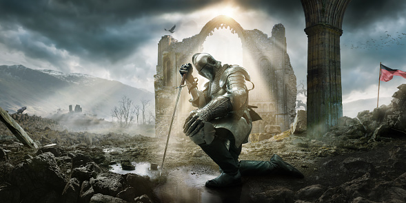 A Medieval knight wearing full suit of armour, boots and chainmail, kneeling as if in defeat or contemplation in preparation for battle. He rests on his sword in a puddle amongst rocks and rubble in front of a building ruin under a dramatic stormy evening sky with rays of sunlight.