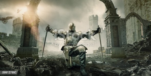 istock Medieval Knight Kneeling With Sword In Front of Building Ruin 599137692