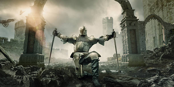 medieval knight kneeling with sword in front of building ruin - warrior person stock pictures, royalty-free photos & images