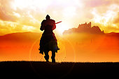 Silhouette of a medieval knight on horse carrying a lance on dramatic scene