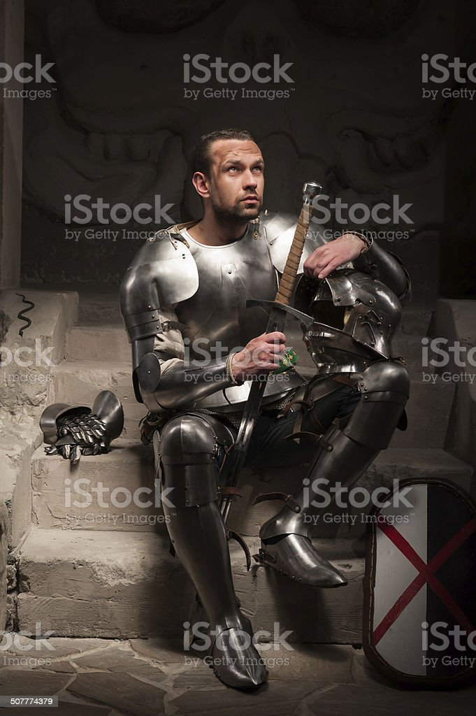 Medieval knight sitting on the steps of ancient temple stock photo