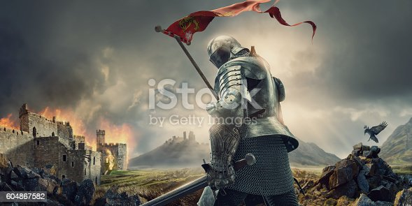 istock Medieval Knight With Banner and Sword Standing Near Burning Castle 604867582