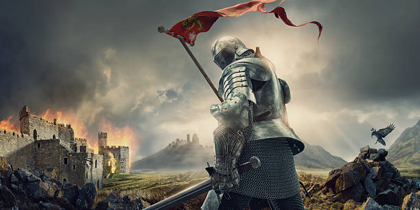 medieval knight with banner and sword standing near burning castle - warrior person stock pictures, royalty-free photos & images