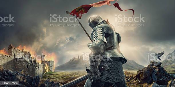 A medieval knight from rear view standing hold a sword and tattered flag, and looking behind himself. The warrior knight is wearing a suit of armour and chainmail, and walks on rocky ground close to a burning ruin of a castle under stormy and dramatic evening sky.