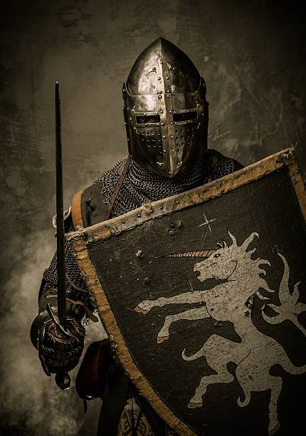 Medieval knight with sword and shield against stone wall stock photo