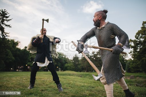 istock Medieval knights swinging axes in a fight 1164553736