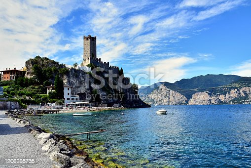Malcesine, Italia - 06.08.2016: Scaliger Castle, a medieval lakeside castle with fortified walls on the shores of Lake Garda, stands on a rock, below the beach, on a crazy plan of the mountain.