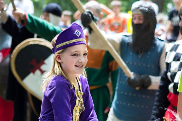 mittelalterliche kleine prinzessin in lila kleid und ritter mit waffe in luft - königin kopfteil stock-fotos und bilder