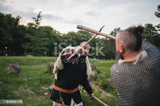 istock Medieval men dueling with axes outdoors 1164555178