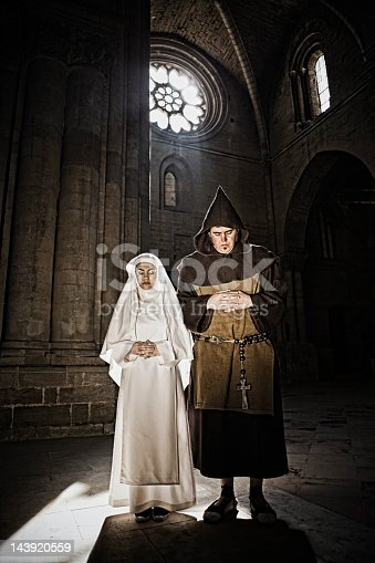 Medieval monk and nun praying in church.