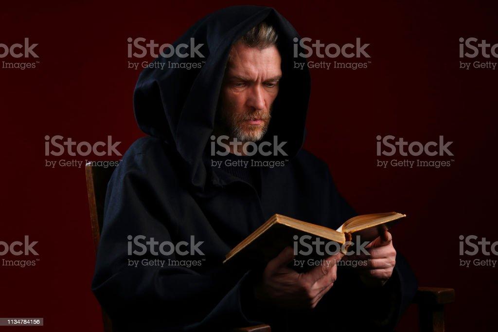 Monge medieval em uma veste preta com um livro em suas mãos - foto de acervo