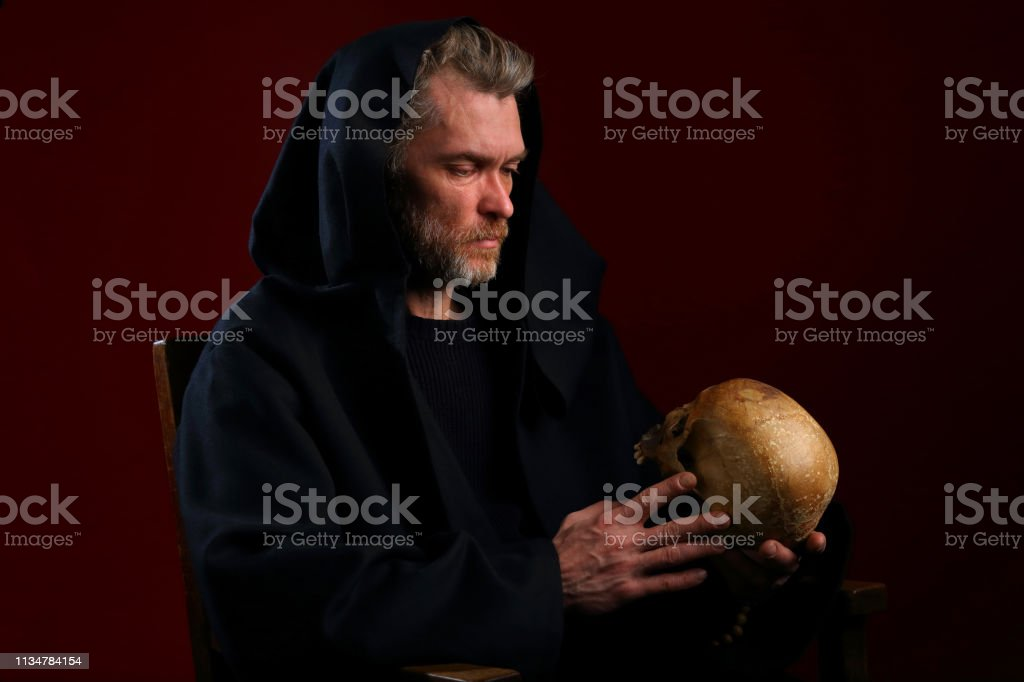 Monge medieval em uma veste preta com um crânio em suas mãos - foto de acervo