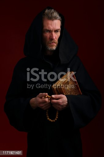 Portrait of a man in a black robe of a medieval monk with books and rosaries