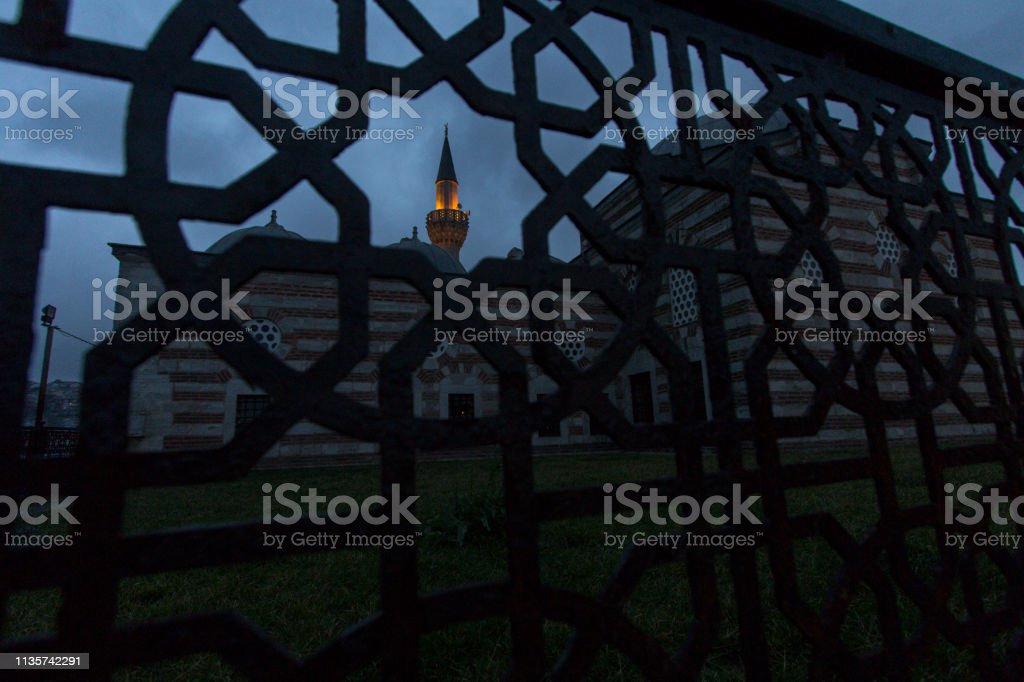 A medieval mosque and its sodium lamp illuminated minaret seen from a forged iron fence with islamic geometric patterns in dusk. Uskudar, Istanbul, Turkey. stock photo