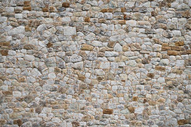 medieval old wall texture and background unique stone exterior - versterkte muur stockfoto's en -beelden