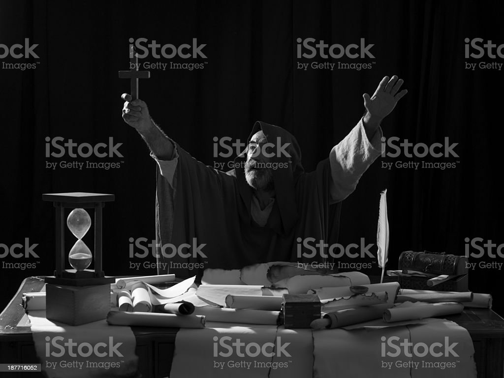 Medieval priest holding cross for praying stock photo