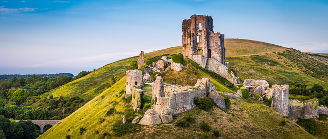 The iconic medieval ruins of Corfe Castle built high a hill in the idyllic Purbeck countryside of Dorset, UK.