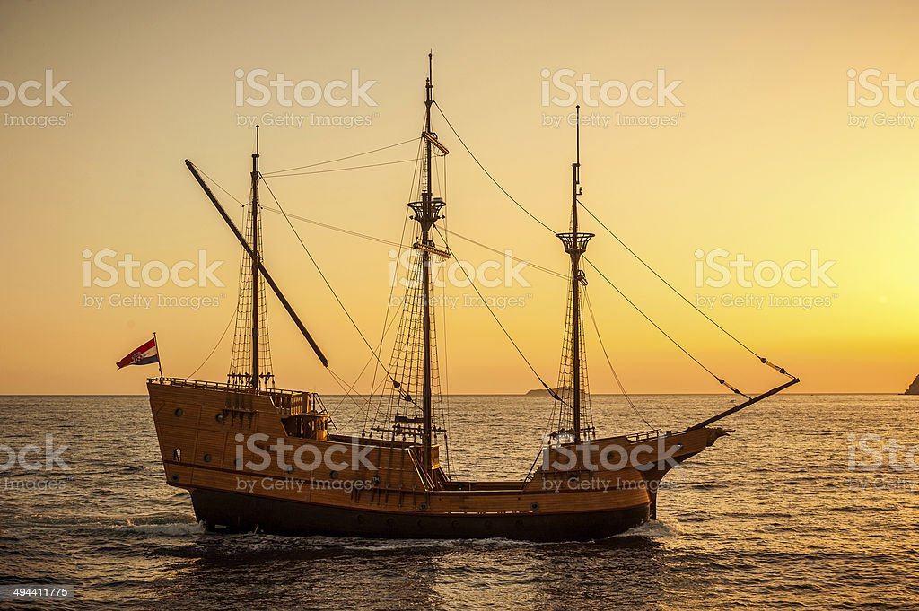 Medieval sailing ship in sunset stock photo