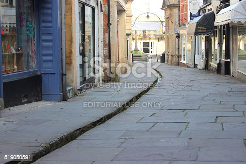 Frome, Somerset, England, UK - September, 11 2014: Image of historic medieval shops and houses lining the pedestrianised, flagstone shopping street of Cheap Street, located in the historic market town of Frome, Somerset, England.  This thoroughfare is particularly unusual, as it has a narrow stream / rill running through the centre of the street, fed by a nearby natural street at the top of the hill.