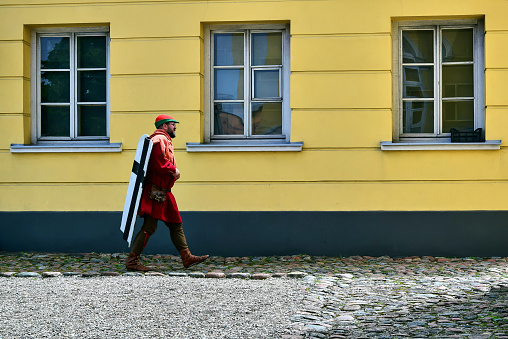 Medieval soldier in red, carries a white cross with a black cross behind him.