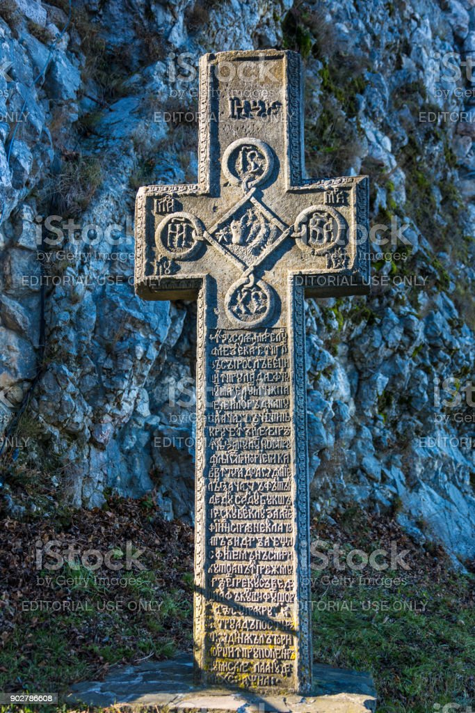 Medieval Stone Cross With Religious Symbols At The Entrance To The