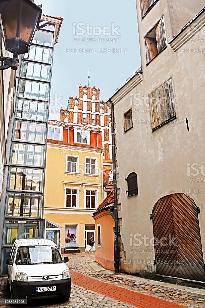 Rua medieval em Riga, Latvia velho. Vista de igreja (vermelho bulding) velho edifício industrial de São João (à esquerda) - foto de acervo