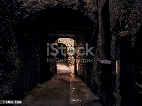 Medieval street / tunnel in Cervera, Spain. Inside a narrow dark stone cave, view of the door