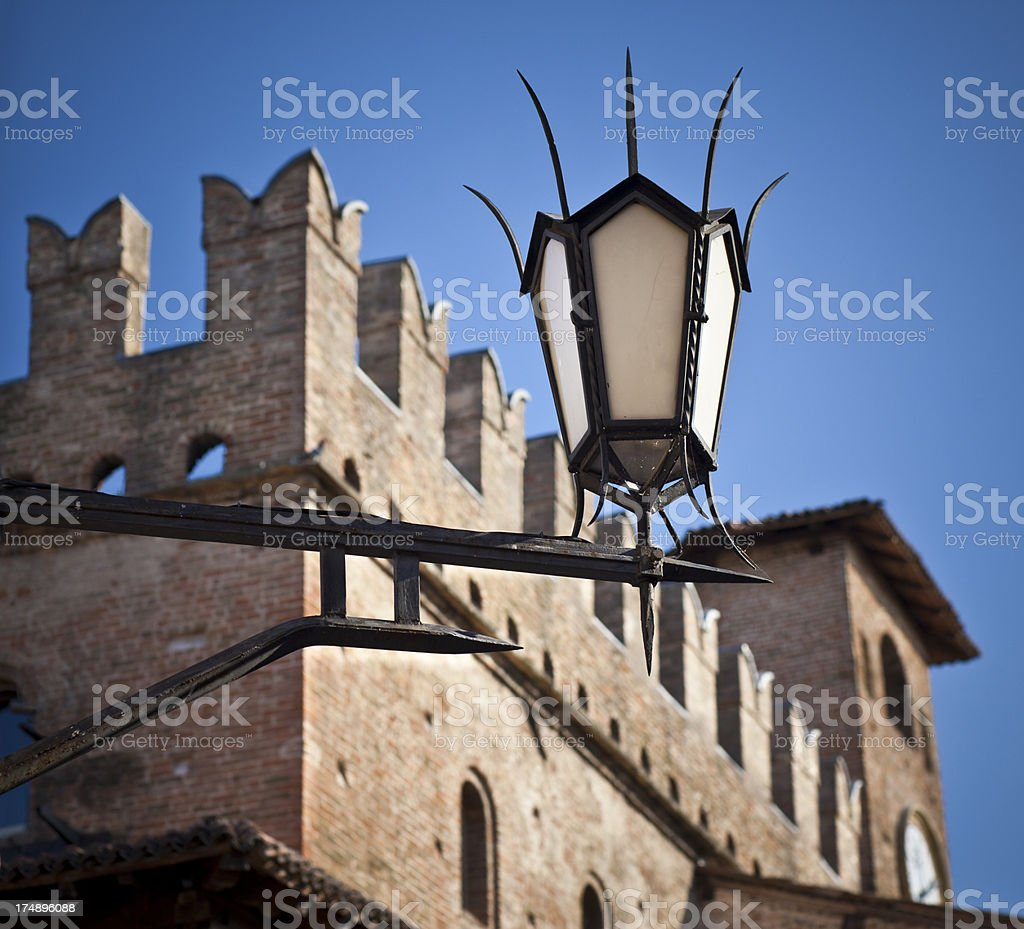Medieval Style Lamp With Clock Palace In The Background, Italy royalty-free stock photo