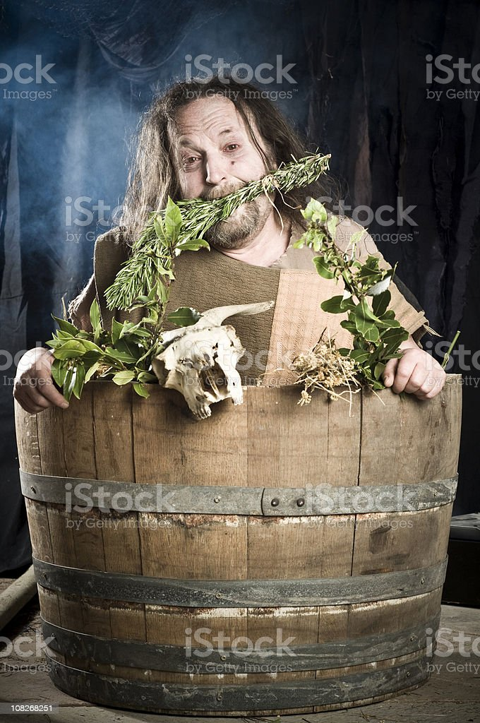 Medieval Style Man in Barrel with Leaves royalty-free stock photo