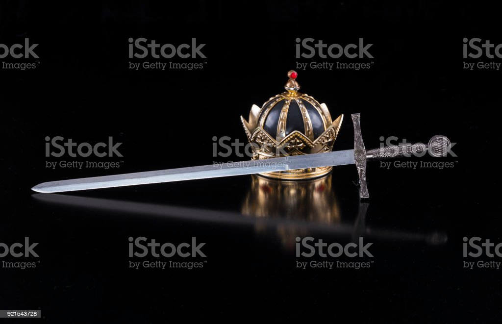 Medieval sword and crown on a black isolated background stock photo