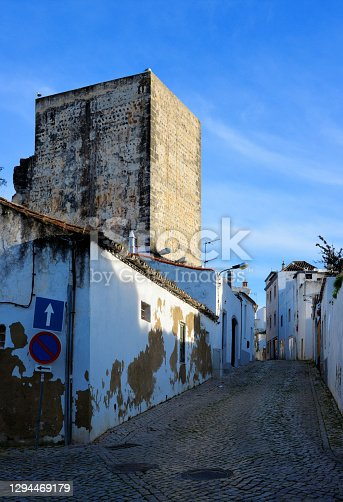 Tavira, Algarve / Faro district, Portugal: view along António Viegas street, with its calçada pavement (cobblestone) and a medieval watch-tower, part of the inner city walls.