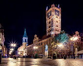 Torun town square with medieval town hall and baroque church.