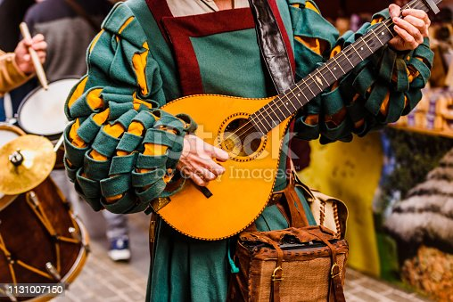 istock Medieval troubadour playing an antique guitar. 1131007150