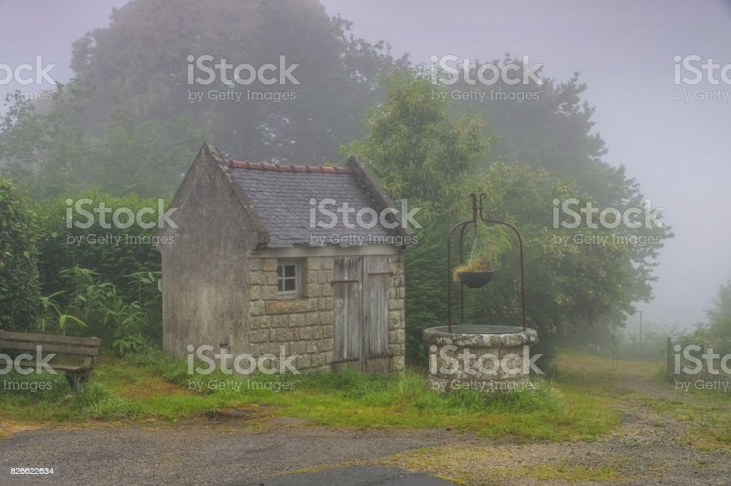 medieval village of Locronan well in fog, Brittany in France stock photo